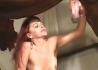 Latina with red hair is giving a handjob to a hot stallion